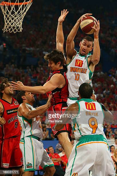 Russell Hinder of the Crocodiles rebounds against Greg Hire of the Wildcats during the round 16 NBL match between the Perth Wildcats and the...