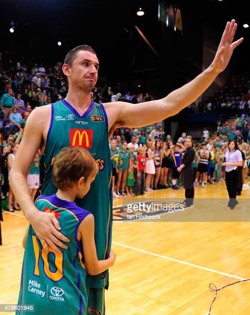 Russell Hinder of the Crocodiles waves to the crowd with his son in his last home game before retirement at the end of the round 22 NBL match between...