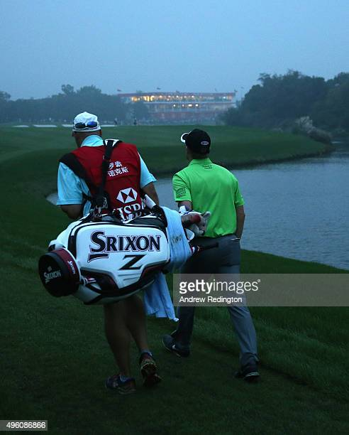 Russell Knox of Scotland and his caddie walk down the 18th hole during the third round of the WGC HSBC Champions at the Sheshan International Golf...