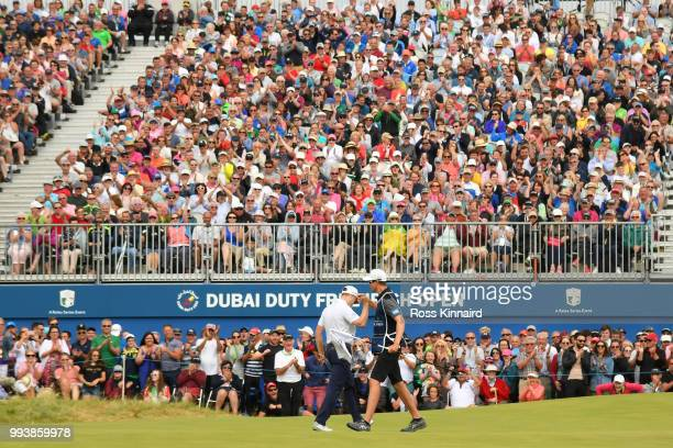 Russell Knox of Scotland celebrates holing a birdie putt on the 18th green with his caddie during the final round of the Dubai Duty Free Irish Open...
