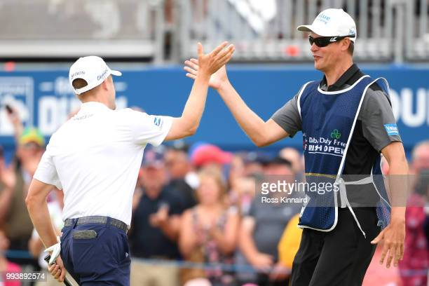Russell Knox of Scotland celebrates holing a putt for victory on the 18th green with his caddie James Williams during a playoff at the end of the...