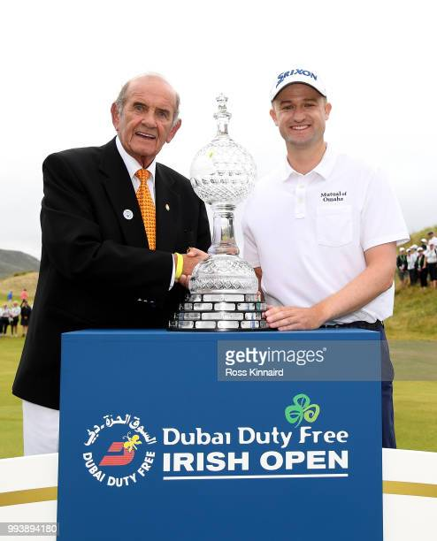 Russell Knox of Scotland is presented with the winners trophy by Colm McLoughlin Executive Vice Chairman and CEO of Dubai Duty Free after his playoff...