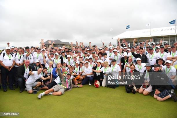 Russell Knox of Scotland poses with marshalls and volunteers following his victory on the 18th green during a playoff at the end of the final round...