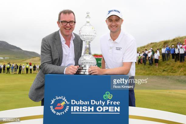 Russell Knox of Scotland poses with the trophy and Chief Executive of the Rory foundation Barry Funston following his victory on the 18th green...