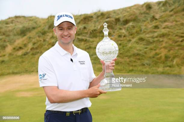 Russell Knox of Scotland poses with the trophy following his victory on the 18th green during a playoff at the end of the final round of the Dubai...