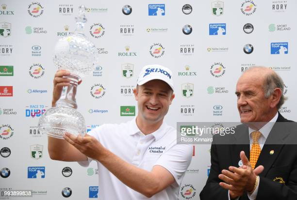 Russell Knox of Scotland receives the trophy from Executive Vice Chairman CEO of Dubai Duty Free Colm Mcloughlin following his victory on the 18th...