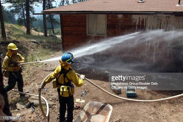 Russell Leadingham left, sprays foam on a home in Big Elk Meadows with the help of another firefighter from the Left Hand Fire District in Boulder...