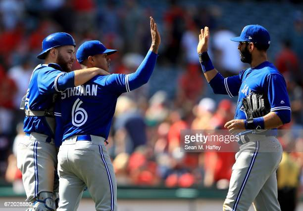 Russell Martin and Jose Bautista congratulate Marcus Stroman of the Toronto Blue Jays after defeating the Los Angeles Angels of Anaheim 62 in a game...