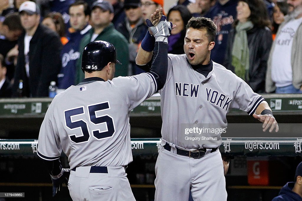Russell Martin #55 and Nick Swisher #33 of the New York Yankees celebrate after Martin scored on a double by Brett Gardner #11 in the seventh inning of Game Three of the American League Division Series at Comerica Park on October 3, 2011 in Detroit, Michigan.