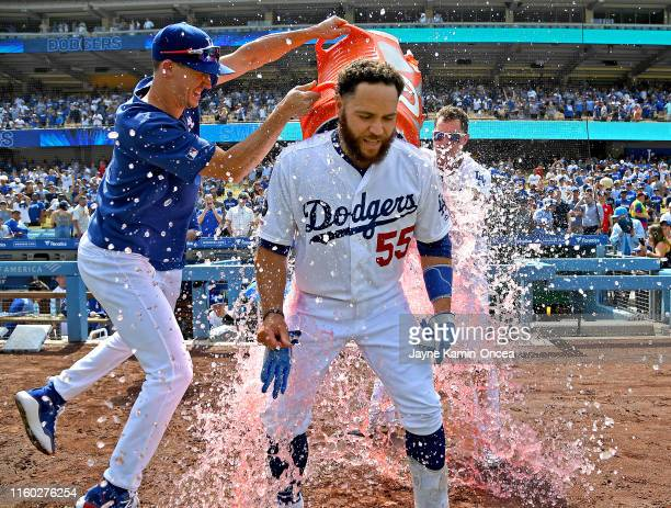 Russell Martin is drenched with a cooler of ice water by Walker Buehler and Joc Pederson as they celebrate his two RBI single for a walkoff win...