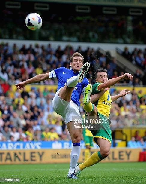 Russell Martin of Norwich City tackled by Nikica Jelavic of Everton during the Barclays Premier League match between Norwich City and Everton at...