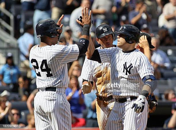 Russell Martin of the New York Yankees celebrates a three run home run with teammates Robinson Cano and Alex Rodriguez against the Tampa Bay Rays at...
