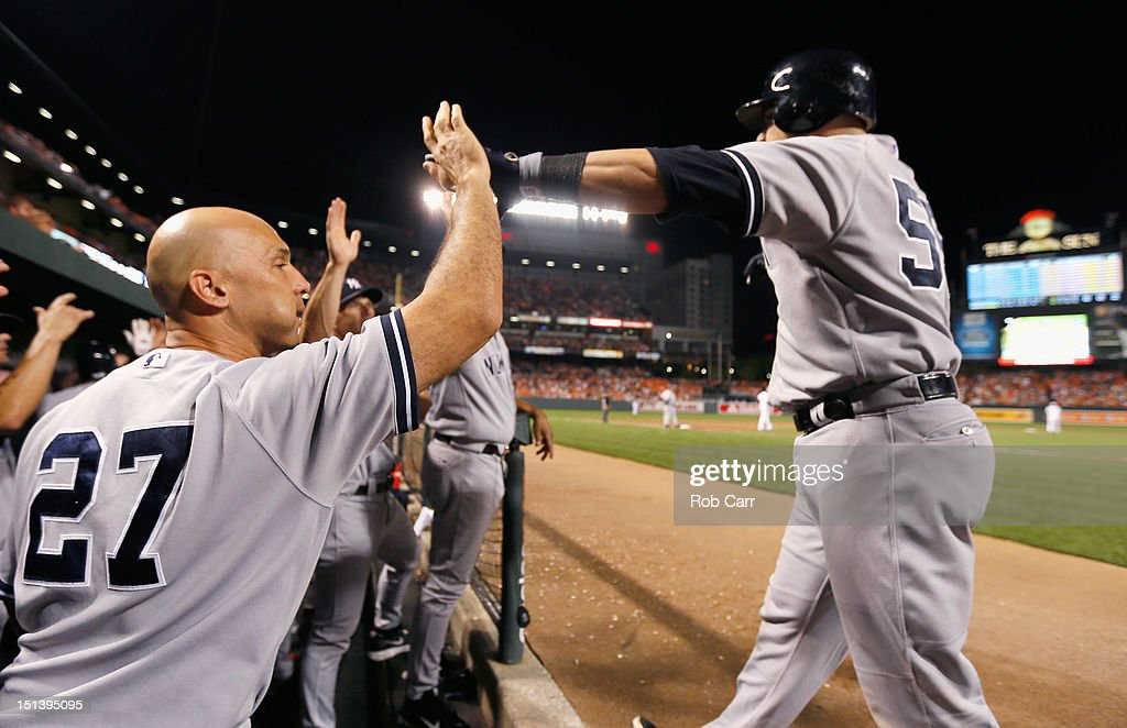 Russell Martin #55 of the New York Yankees celebrates after scoring a run with teammate Raul Ibanez #27 during the eighth inning against the Baltimore Orioles at Oriole Park at Camden Yards on September 6, 2012 in Baltimore, Maryland.