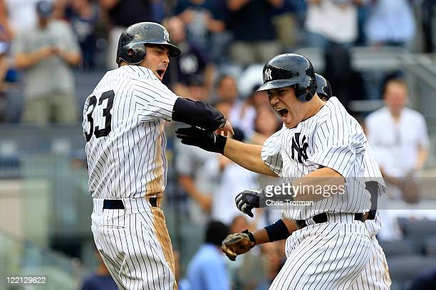 Russell Martin of the New York Yankees is congratulated by teammate Nick Swisher on his grand slam home run in the sixth inning against the Oakland...