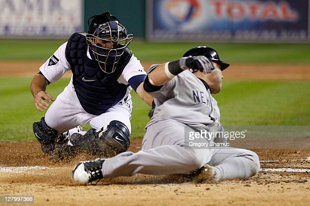 Russell Martin of the New York Yankees slides in to home plate safe ahead of the tag of Alex Avila of the Detroit Tigers in the third inning of Game...