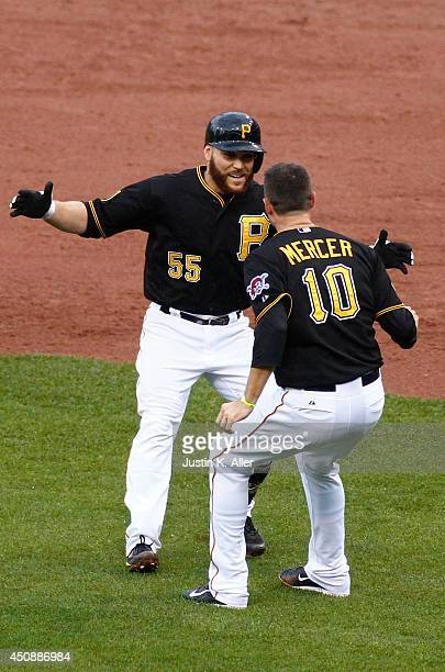 Russell Martin of the Pittsburgh Pirates celebrates with Jordy Mercer after being walked with the bases loaded in the bottom of the twelfth inning...