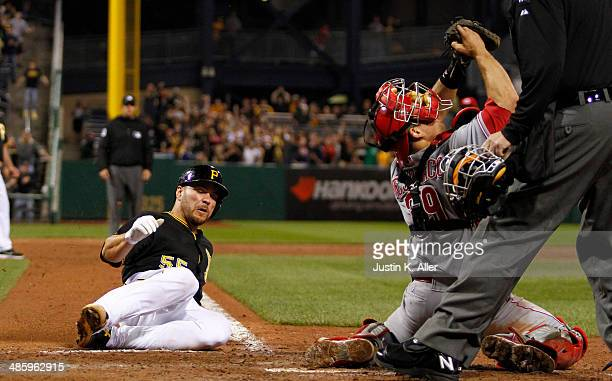 Russell Martin of the Pittsburgh Pirates scores on a RBI walk off single in the ninth inning Devin Mesoraco of the Cincinnati Reds during the game at...
