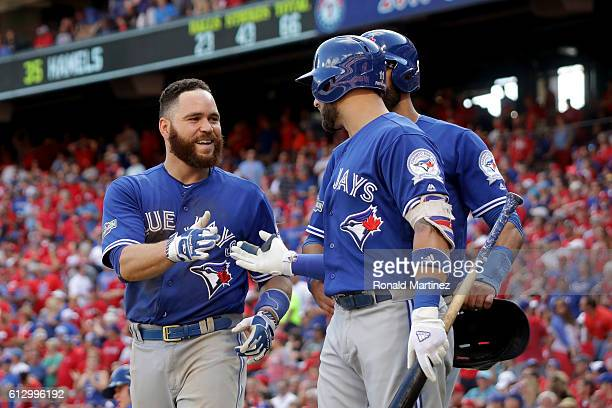 Russell Martin of the Toronto Blue Jays celebrates with his teammates after scoring a run off of Troy Tulowitzki RBI triple to right field against...