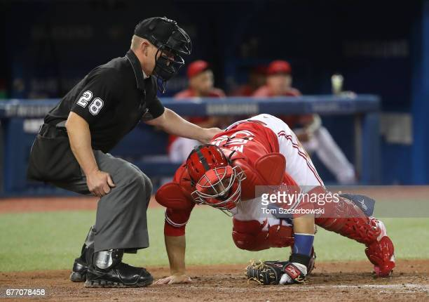Russell Martin of the Toronto Blue Jays falls after absorbing a foul tip as home plate umpire Jim Wolf helps him stay up during MLB game action...