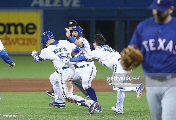Russell Martin of the Toronto Blue Jays is congratulated by Darwin Barney and Kevin Pillar after hitting a gamewinning RBI single in the ninth inning...