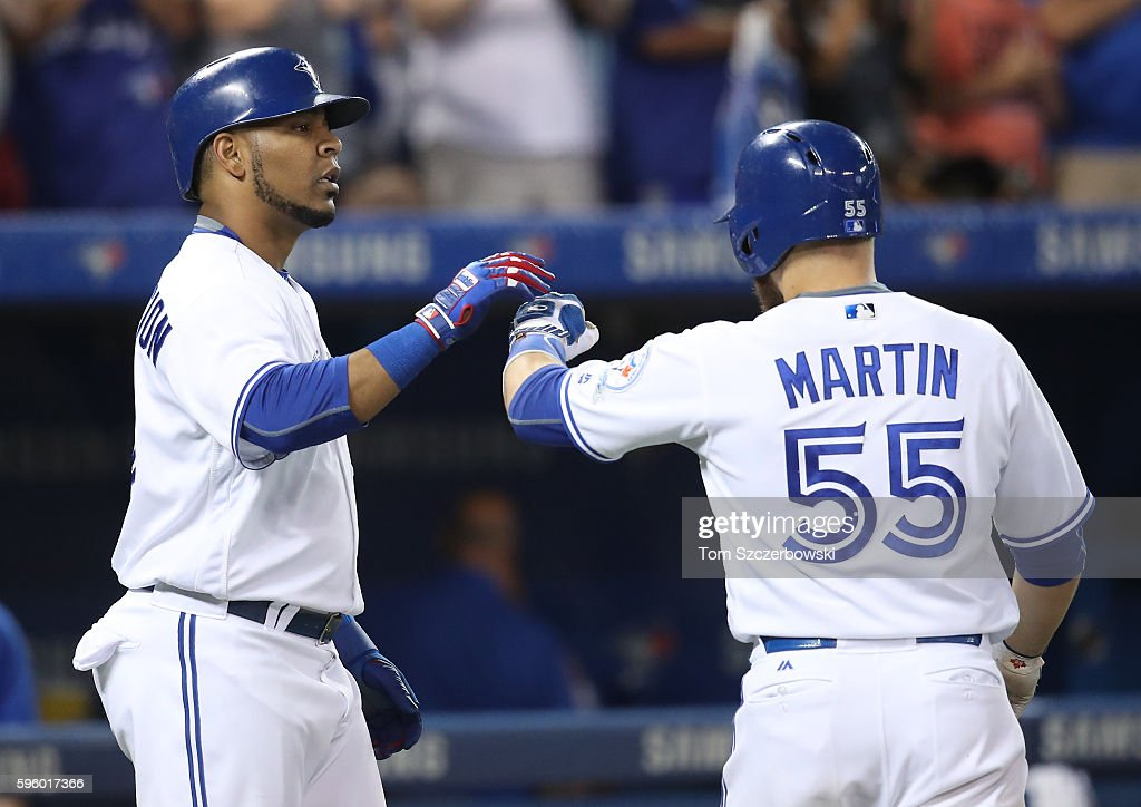 Russell Martin #55 of the Toronto Blue Jays is congratulated by Edwin Encarnacion #10 after hitting a two-run home run in the seventh inning during MLB game action against the Minnesota Twins on August 26, 2016 at Rogers Centre in Toronto, Ontario, Canada.