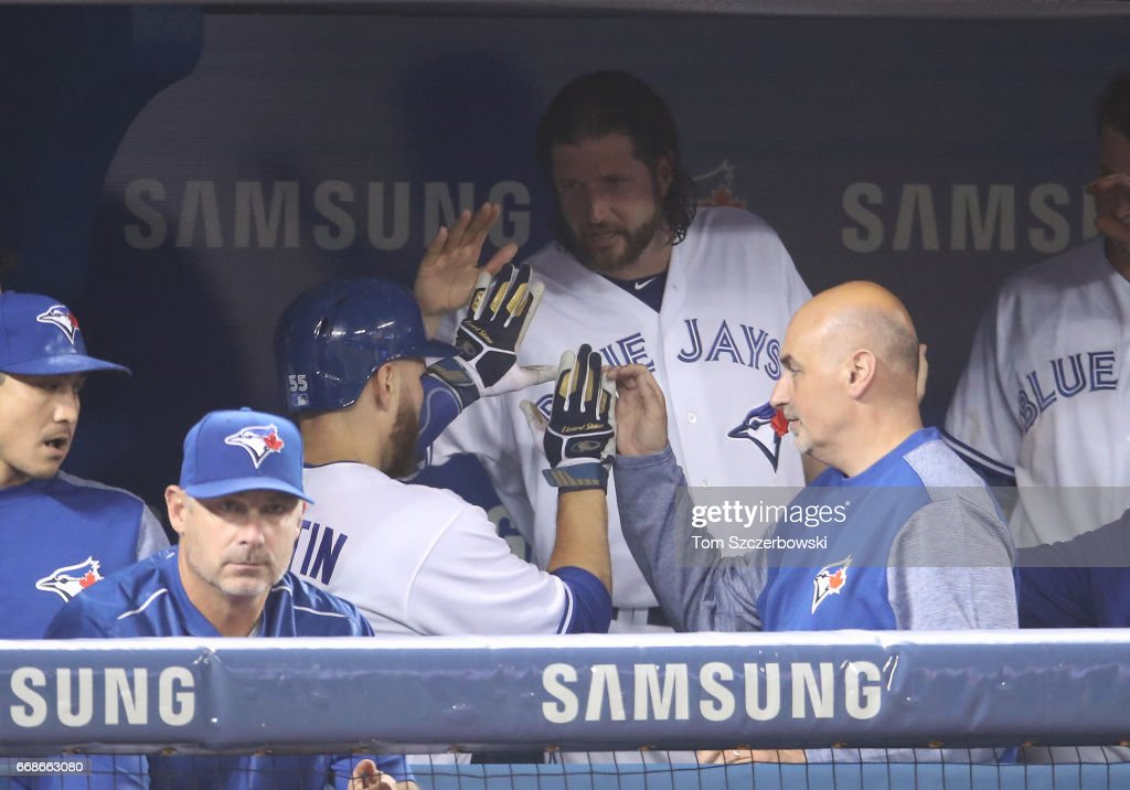 Russell Martin #55 of the Toronto Blue Jays is congratulated by Jason Grilli #37 after scoring a run in the ninth inning during MLB game action against the Baltimore Orioles at Rogers Centre on April 14, 2017 in Toronto, Canada.