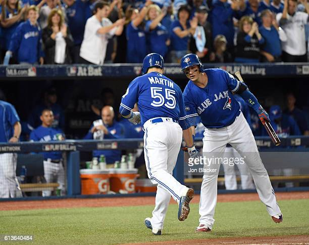 Russell Martin of the Toronto Blue Jays is congratulated by teammate Troy Tulowitzki after hitting a home run in the bottom of the first inning of...