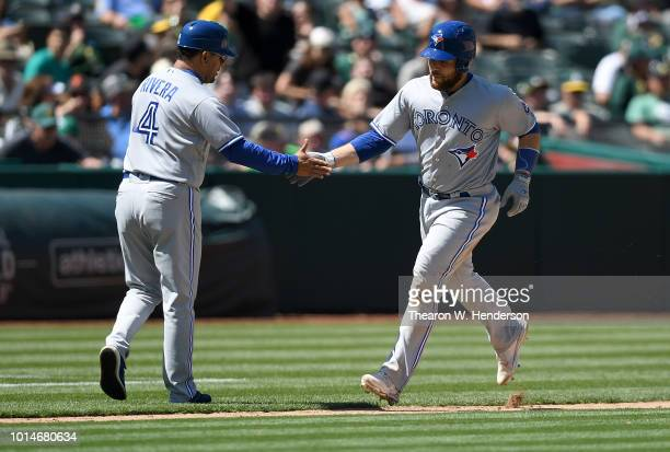 Russell Martin of the Toronto Blue Jays is congratulated by third base coach Luis Rivera after Martin hit a tworun home run against the Oakland...