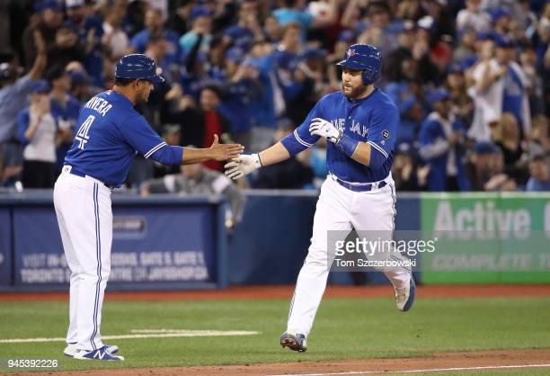 Russell Martin of the Toronto Blue Jays is congratulated by third base coach Luis Rivera after hitting a tworun home in the seventh inning during MLB...