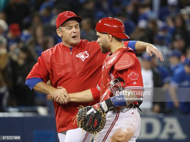 Russell Martin of the Toronto Blue Jays is congratulated on their victory by manager John Gibbons during MLB game action against the Tampa Bay Rays...
