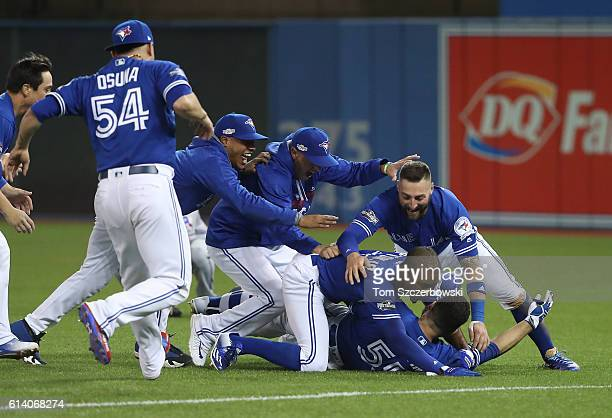 Russell Martin of the Toronto Blue Jays is mobbed by Melvin Upron Jr #7 and Kevin Pillar and teammates after the gamewinning run scored in the tenth...