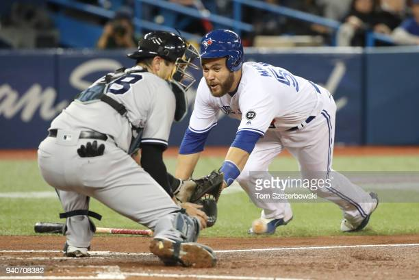 Russell Martin of the Toronto Blue Jays is tagged out at home plate by Austin Romine of the New York Yankees in the second inning during MLB game...