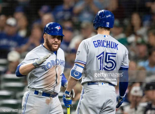 Russell Martin of the Toronto Blue Jays isx congratulated by Randal Grichuk of the Toronto Blue Jays after scoring on a sacrifice fly by Kevin Pillar...