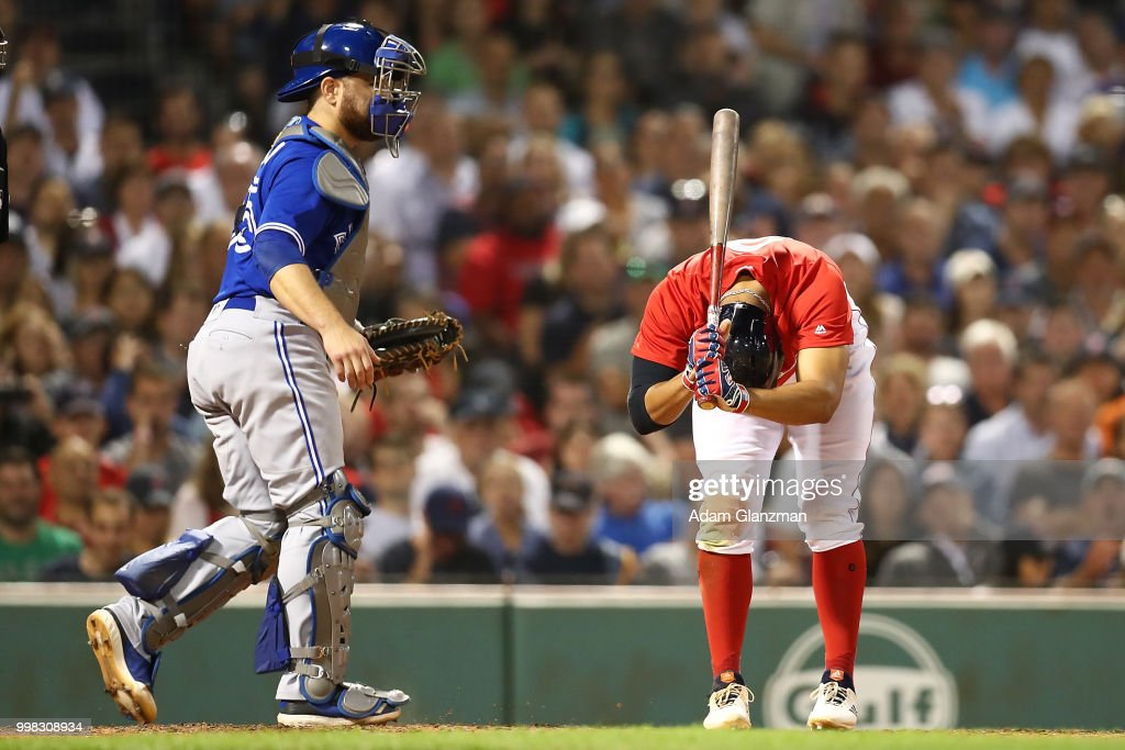 Russell Martin #55 of the Toronto Blue Jays looks on as Mookie Betts #50 of the Boston Red Sox reacts after striking out in the fifth inning of a game at Fenway Park on July 13, 2018 in Boston, Massachusetts.