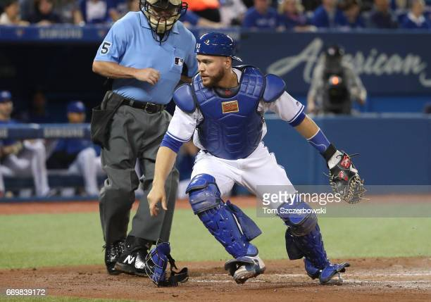 Russell Martin of the Toronto Blue Jays reacts as a wild pitch goes to the backstop in the second inning during MLB game action against the Baltimore...