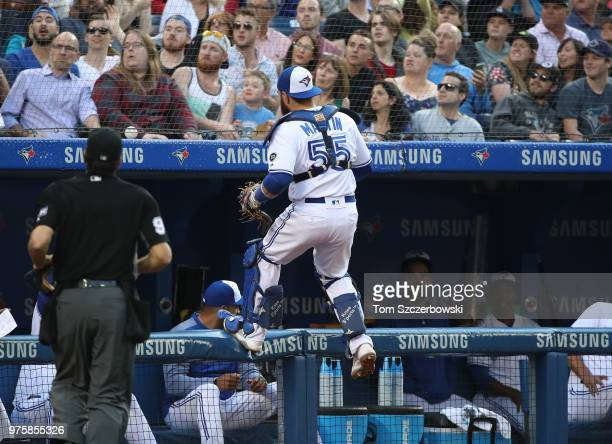 Russell Martin of the Toronto Blue Jays runs after a foul ball out of play and climbs the railing on the Blue Jays dugout in the third inning during...