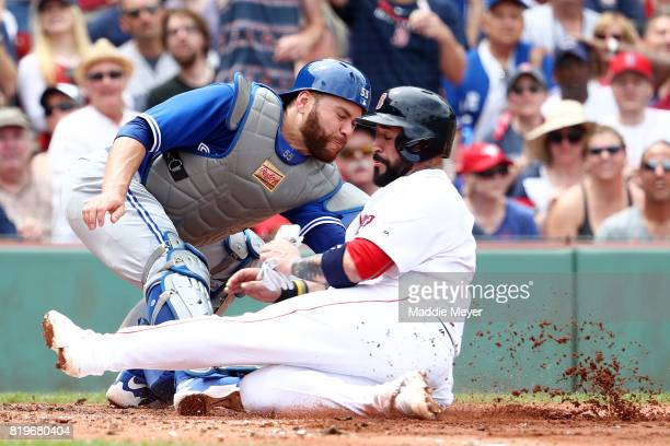Russell Martin of the Toronto Blue Jays tags out Sandy Leon of the Boston Red Sox at home during the second inning at Fenway Park on July 20 2017 in...