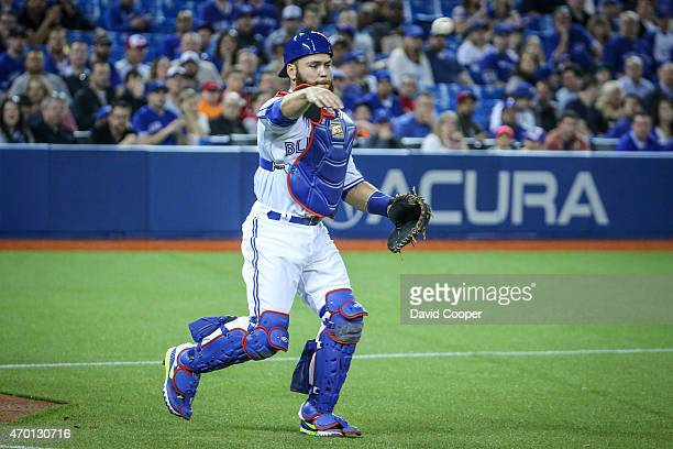 Russell Martin of the Toronto Blue Jays throws to first to get Alberto Callaspo of the Atlanta Braves on a weak ground ball in front of the plate...