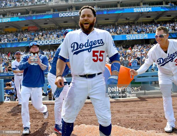 Russell Martin reacts after getting doused with sports drink by Alex Verdugo Walker Buehler and Joc Pederson of the Los Angeles Dodgers after hitting...