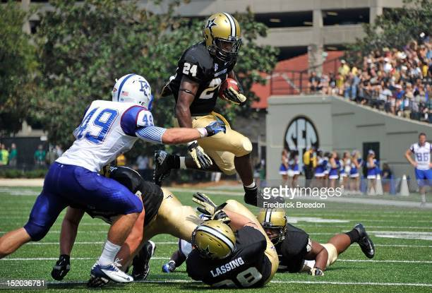 J Russell of the Presbyterian Blue Hose watches Wesley Tate of the Vanderbilt Commodores jump over teammate Fitz Lassing on the way to the end zone...