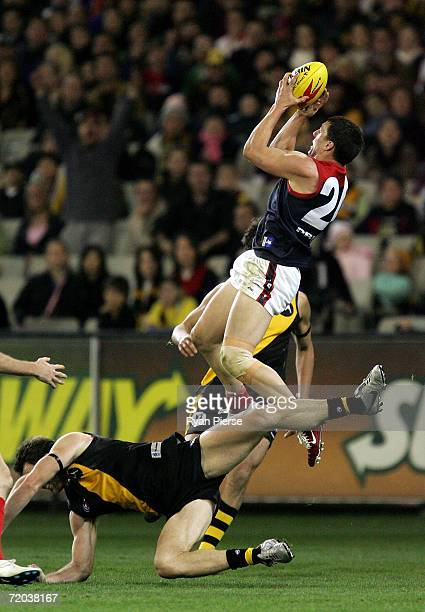 Russell Robertson of the Demons takes a high mark over Joel Bowden of the Tigers during the round 15 AFL match between the Richmond Tigers and the...