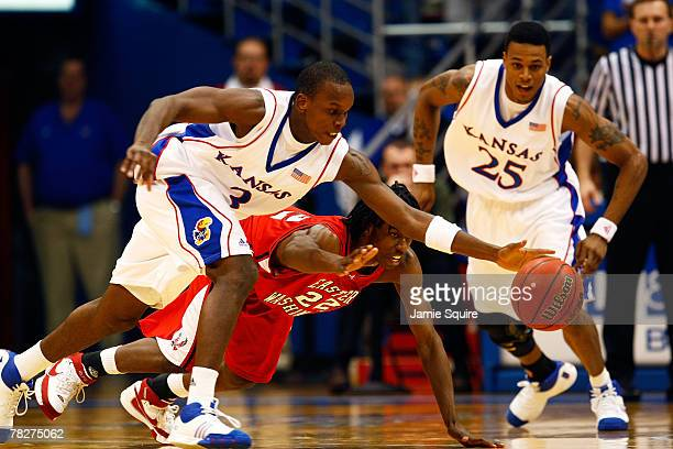 Russell Robinson of the Kansas Jayhawks steals the ball from Trey Gross of the Eastern Washington Eagles as Brandon Rush looks on during the game on...