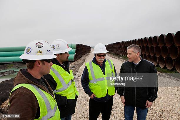 Russell Russ Girling president and chief executive officer of TransCanada Corp right speaks with workers during a media event at the TransCanada Corp...