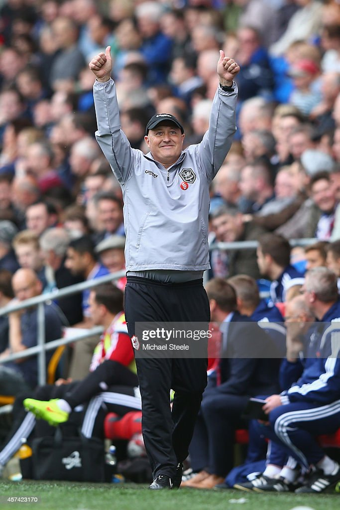 Russell Slade the new manager of Cardiff City salutes the home supporters during the Sky Bet Championship match between Cardiff City and Nottingham Forest at Cardiff City Stadium on October 18, 2014 in Cardiff, Wales.