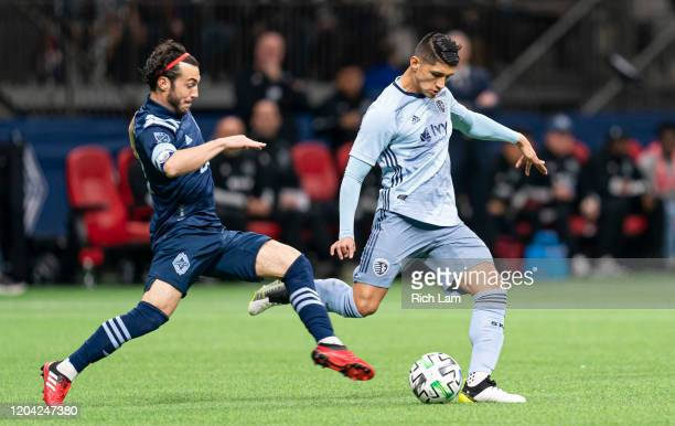 Russell Teibert of the Vancouver Whitecaps challenges Alan Pulido of Sporting Kansas City during MLS soccer action at BC Place on February 29 2020 in...