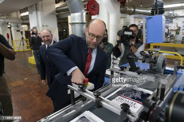 Russell Vought acting director of the Office of Management and Budget presses the start button of a machine to bind copies of US President Donald...