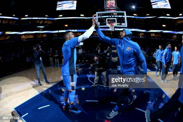 Russell Westbrook and Carmelo Anthony of the Oklahoma City Thunder high five before the game against the Memphis Grizzlies on December 9 2017 at...