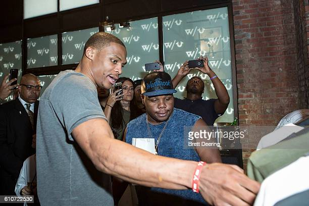 Russell Westbrook and his brother Raynard look at some clothing from the True Religion x Russell Westbrook Collection during the True Religion x...