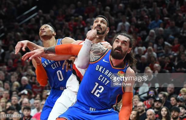 Russell Westbrook and Steven Adams of the Oklahoma City Thunder battle for position with Enes Kanter of the Portland Trail Blazers at Moda Center on...