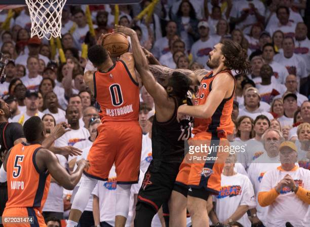 Russell Westbrook and Steven Adams of the Oklahoma City Thunder try to trap James Harden of the Houston Rockets as he tries to shoot during the...